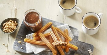 Churros with hot chocolate and nutty topping